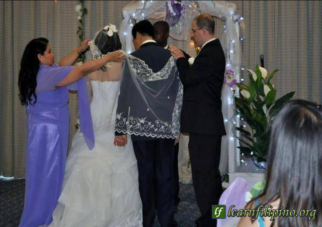 "In a Filipino wedding, parts of the ceremony are the placing of veil and cord by the Sponsors. Veil – It is a symbol of purity. It symbolizes the presence of the Lord. It is placed over the shoulders of the couple to symbolize their union and being ""clothed as one"" in unity. Cord – It is a symbol of the couple's bond; that they are no longer two but one in their new life as a couple."
